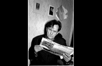 Shalamov reading a newspaper. On the wall are pictures of Osip Mandelstam. 1968. Photo: shalamov.ru